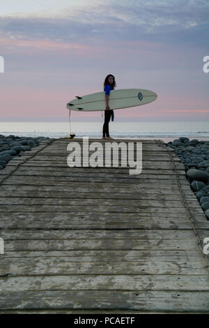 Female surfer standing on pebble ridge with surfboard before heading off into the sea to surf at Westward Ho! beach, North Devon, England, Europe. - Stock Image