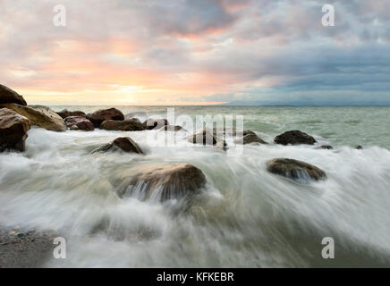 Ocean waves sunset is a surreal ocean sunset with water rushing to the shore as the sun sets on the ocean horizon. - Stock Image