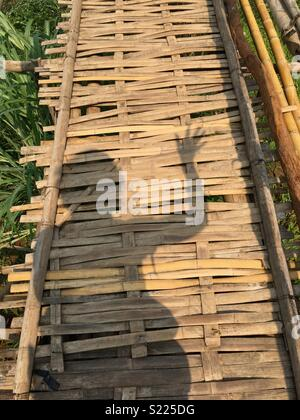 Shadow waving crossing a bamboo bridge In Laos - Stock Image