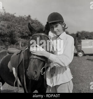 1967, young girl stroking the forehead of her horse, England, UK. - Stock Image