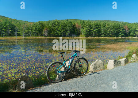 Mountain bike parked on a carriage road  edging Eagle Lake in Acadia National Park, Maine, USA. - Stock Image