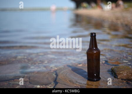 Brown glass bottle with a rippling water background and tourists in the background with selective focus and blur - Stock Image