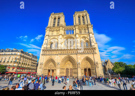 Paris, France - July 1, 2017: many tourists in square of Notre Dame de Paris, Ile de la Cite, while they wait to visit the famous gothic church. Sunny day, blue sky. Main facade of Cathedral of Paris. - Stock Image