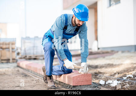 Builder in uniform mounting road borders on the construction site - Stock Image