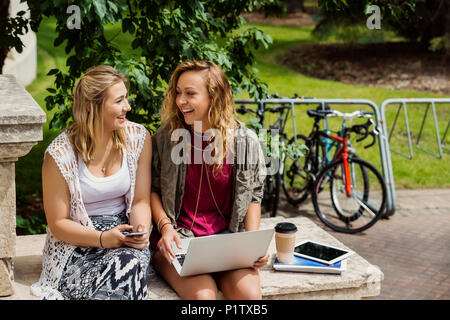 Two female university students laughing and talking together while using their technology outside on the campus; Edmonton, Alberta, Canada - Stock Image