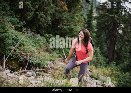 Happy young woman hiking in woods - Stock Image