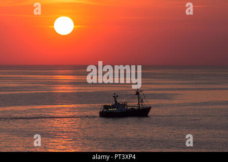 A fishing trawler on the North Sea off the coast of Belgium at sunset. - Stock Image
