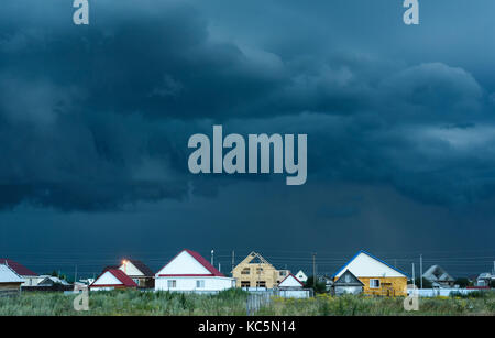Dark blue and black rain clouds gather over village homes and houses as a storm begins - Stock Image