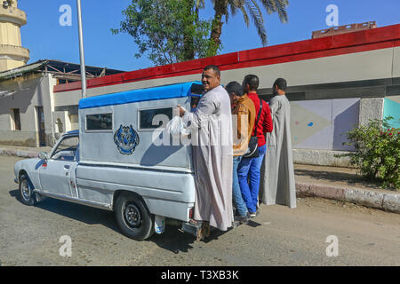 4 Arab men hitching a lift on the back of a truck at Aswan, Egypt, Africa - Stock Image