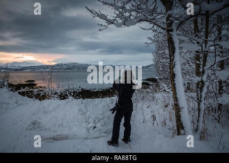 Female photographer capturing winter snows at Finnsnes, Norway. - Stock Image