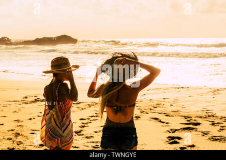 Sunset light at the beach with people enjoying the outdoor holiday vacation leisure - couple of women friends enjoying the nature in tropical scenic p - Stock Image