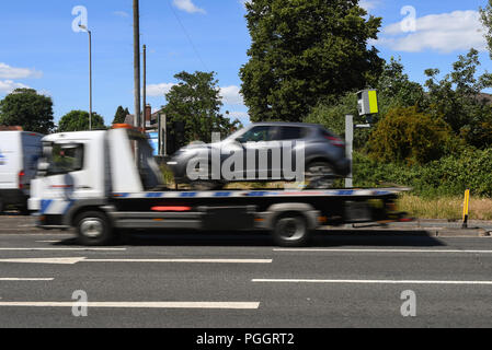 A red light traffic offence camera with cars blurring by. - Stock Image