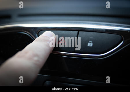 A finger pressing the hazard warning light on a car interior - Stock Image