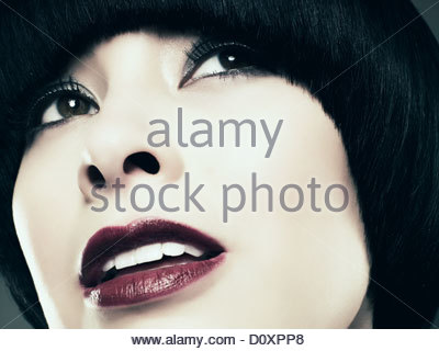 Young woman with black bob looking away, close up - Stock Image