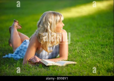 Girl lying in park - Stock Image