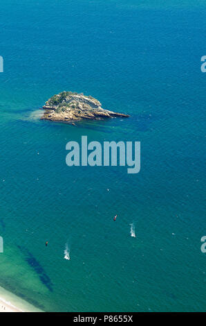 Two kitesurfers, seen from far and above, surfing over blue and green waters facing Portinho da Arrabida beach at Serra da Arrabida. Small island in v - Stock Image