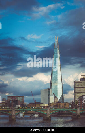 The Shard reflecting the soft evening light against a stormy sky - Stock Image