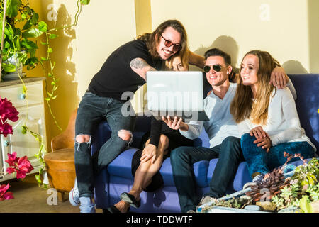 Group of young caucasian friends people have fun and laugh sitting on the sofa with laptop compuer and internet connection - millennial lifestyle for  - Stock Image