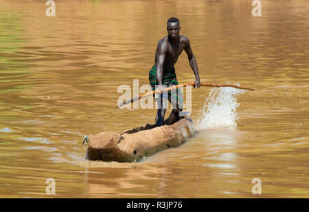 Kara tribe, man paddling a dugout canoe on Lower Omo River, Turmi, South Omo, Ethiopia - Stock Image