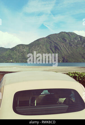 rear view of a convertible car parked in front of Lake Como, Italy - Stock Image