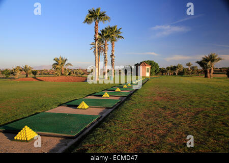 Tropical golf driving range practice with golf balls stacked in pyramids. - Stock Image