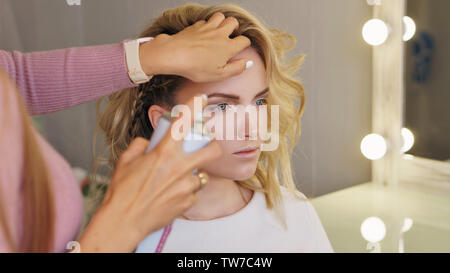 Stylish attractive blonde in beauty salon. Girl makes an evening hairstyle at professional hairdresser. Hair stylist uses spray-shaped hairspray to fi - Stock Image