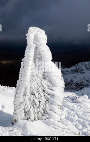 Ice covered marker stone at top of Watkin Path on Mount Snowdon in winter snow in Snowdonia National Park. Rhyd Ddu, Gwynedd, North Wales, UK, Britain - Stock Image