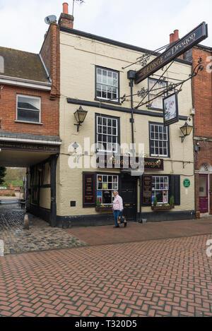 A lone elderly lady walking past the George and Dragon pub, High Street, Chesham, Buckinghamshire, England, UK - Stock Image