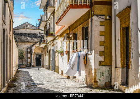 A residential alley with laundry hanging from a window leads to the entrance of the Church of San Giovanni al Sepolcro in the city of Brindisi, Italy - Stock Image