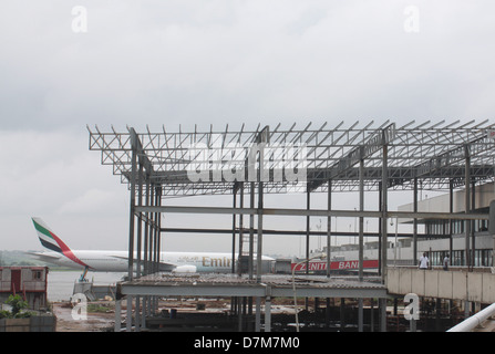 An aircraft parked at the E finger of the Murtala Muhammed Airport, Lagos framed against the ongoing construction - Stock Image