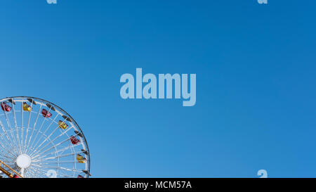 Cropped shot of a Ferris wheel against blue clear sky with copy space, concept for freedom, enjoyment, amusement park and nostalgia for childhood fun - Stock Image