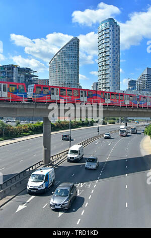 East End high rise skyscraper apartment building towering over train on docklands light railway viaduct above traffic on road Tower Hamlets London UK - Stock Image