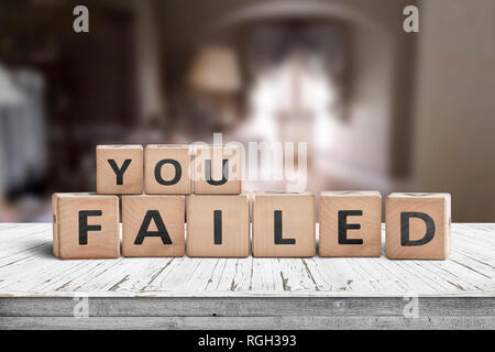 You failed sign on a wooden table in a dark room with light at the end - Stock Image