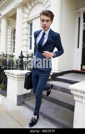 Young man in checked suit leaving smart London house - Stock Image