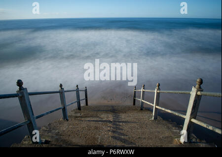 A long exposure image of the waves crashing against Whitby beach on the North Yorkshire coast - Stock Image