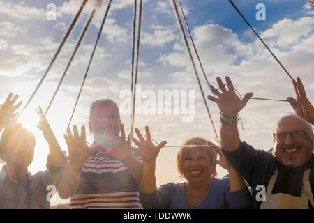 Concept of people friendship and team with group of senior caucasian grandfathers connected with cord together during funny celebration outdoor - blue - Stock Image