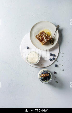 Homemade classic dessert Panna cotta with blueberry berries in jars, decorated by mint, thym, honey combs over grey texture background. Flat lay, spac - Stock Image