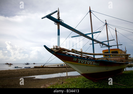 A fishing boat under repair rests on the beach in Mansalay, Oriental Mindoro, Philippines. - Stock Image
