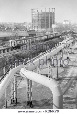 An electric train passing by Reading Gasworks, Berkshire, UK – 1985 - Stock Image