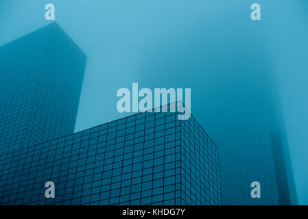Tall skyscrapers disappearing into fog - Stock Image