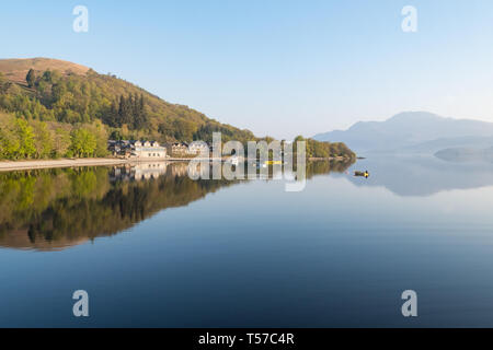 Luss, Loch Lomond, Scotland, UK. 22nd Apr, 2019. uk weather - a glorious still and hazy morning at Luss, Loch Lomond, overlooking the distinctive outline of Ben Lomond ahead of what is forecast to be a beautiful sunny day Credit: Kay Roxby/Alamy Live News - Stock Image