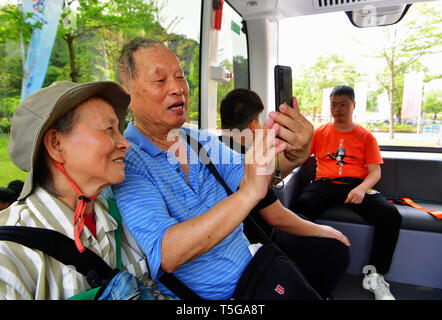 Fuzhou, China's Fujian Province. 24th Apr, 2019. Passengers sit in a self-driving bus running on a sight-seeing path in the Feifeng Moutain smart park in Fuzhou, capital of southeast China's Fujian Province, April 24, 2019. The Feifeng Mountain smart park, the first AI park of Fujian province, opened in Fuzhou recently. Credit: Wei Peiquan/Xinhua/Alamy Live News - Stock Image