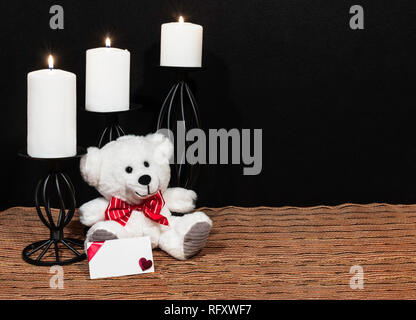 Cudlely teddy bear with red bow tie, white candles perched on black candle holders on mesh place mat and wooden table with card and dark background. V - Stock Image