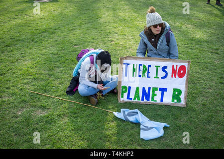A mother and child sit on the grass with a 'There is no Planet B' banner on Parliament Green, Westminster for the Extinction Rebellion demonstration - Stock Image