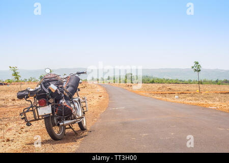 An old packed motorcycle parked by a desert road. - Stock Image