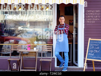 Portrait of a confident young man standing in the doorway of a coffee shop. Tea and Coffee Shop written on the window. Traffic reflection. His welcomi - Stock Image