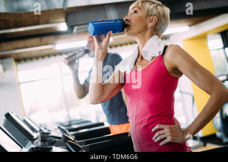 Mature woman drinking water in gym after workout - Stock Image