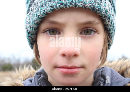 Portrait of a girl with intense green eyes wearing a cap in the winter cold - Stock Image