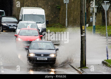 Chippenham, Wiltshire, UK. 12th Mar, 2019. Car drivers are pictured braving heavy rain in Chippenham as heavy rain showers make their way across the UK. Credit: lynchpics/Alamy Live News - Stock Image