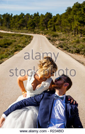 Couple of newlyweds pose in romantic attitude in the middle of a lonely road - Stock Image